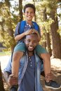 Portrait Of Father Walking In Woods Carrying Son On Shoulders Royalty Free Stock Photo