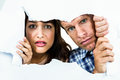 Portrait of fearful couple peeking through torn paper Royalty Free Stock Photography