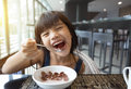 Portrait of feeling happy a young girl having breakfast on table