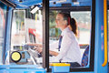 Portrait of female bus driver behind wheel holding steering smiling Stock Images
