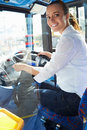 Portrait of female bus driver behind wheel sitting down looking back at camera smiling Royalty Free Stock Photos