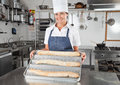 Portrait female chef presenting baked breads restaurant kitchen Royalty Free Stock Image