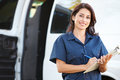 Portrait of female delivery driver with clipboard smiling to camera Stock Image