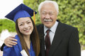Portrait of a female graduate and grandfather happy standing outdoors Royalty Free Stock Images