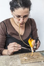 Portrait of a female jeweler working with a flame on a piece of silver wire Stock Images