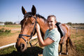 Portrait of female jockey fastening bridle Royalty Free Stock Photo