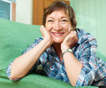 Portrait of female pensioner woman relaxing in couch Royalty Free Stock Photo