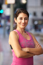 Portrait of female runner on urban street smiling Stock Photo