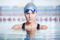 Portrait of a female swimmer wearing swimming cap and goggles in blue water swimming pool sport woman Stock Images