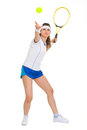 Portrait of female tennis player serving ball full length Stock Images