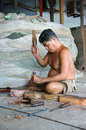 Portrait of fisherman pare wood at fishing net shop in vertical frame ca mau viet nam june the man with carpentry tool bore a hole Royalty Free Stock Image