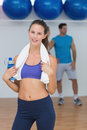Portrait of a fit female holding water bottle with a man in background at gym Royalty Free Stock Photo