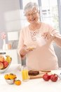 Portrait of fit granny elderly lady preparing healthy breakfast with cereal orange juice and fruits Royalty Free Stock Photo
