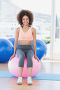 Portrait of a fit woman sitting on fitness ball at gym full length young bright Royalty Free Stock Photography