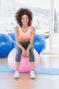 Portrait of a fit woman sitting on fitness ball at gym full length young bright Stock Image