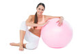 Portrait of a fit woman sitting with fitness ball Royalty Free Stock Photo