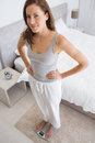 Portrait of a fit woman standing on scale in bedroom Royalty Free Stock Photo