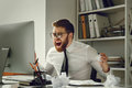 Frustrated businessman in panic sitting at his working place Royalty Free Stock Photo