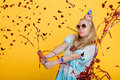 Portrait of funny blond woman in birthday hat and red confetti on yellow background. Celebration and party. Royalty Free Stock Photo