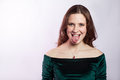 Portrait of funny crazy woman with freckles and classic green dress with tongue. Royalty Free Stock Photo