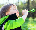 Portrait of funny little boy blowing soap bubbles Stock Photo