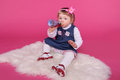 Portrait of funny little girl drinking water sitting on fur over pink background Royalty Free Stock Image
