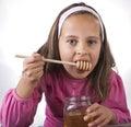 Portrait of funny lovely little girl eat honey Royalty Free Stock Photo