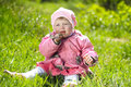 Portrait of funny lovely little girl sitting on a green grass outdoors Royalty Free Stock Images
