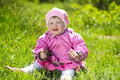 Portrait of funny lovely little girl sitting on a green grass outdoors Royalty Free Stock Photography