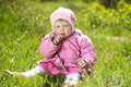 Portrait of funny lovely little girl sitting on a green grass outdoors Royalty Free Stock Photo