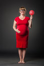 Portrait of funny pregnant woman in red dress Royalty Free Stock Photo