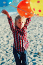 Portrait of funny white Caucasian child kid boy with colorful bunch of  balloons, playing running on beach on sunset Royalty Free Stock Photo