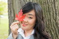 Portrait of girl during autumn cute young woman in front a maple tree holding a maple leaf and covering her eye Stock Photography