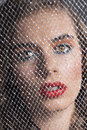 Portrait of girl behind net looks in to the lens Stock Image