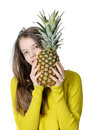 Portrait of a girl with a big pineapple in hands.