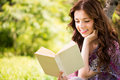 Portrait of girl with a book in the park beautiful reading sitting on grass and expressing positivity Royalty Free Stock Photo