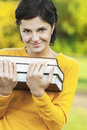 Portrait of girl with books young woman in yellow sweater holds three in hands Stock Image