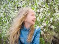 Girl with her hair down in a denim shirt in a cherry blossom garden. Portrait of laughing happy girl. Royalty Free Stock Photo