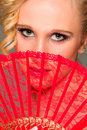 Portrait of girl closing face with textile fan Royalty Free Stock Photo