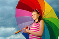 Portrait of girl with colorful umbrella looking towards the light Stock Photography