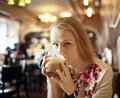 Portrait girl enjoying coffee latte cafe looking to photographer beautiful vintage interior blur natural sunlight Royalty Free Stock Photography