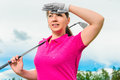 Portrait of a girl with a golf club looking out for the flight path the ball Royalty Free Stock Images