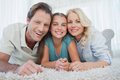 Portrait of a girl and her parents lying on a carpet in the living room Royalty Free Stock Images