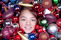 Portrait of girl in ornaments a young girls face shows out a bunch christmas Stock Images