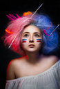 Portrait of the girl painter with color paint on face with tattoo on hand and brushes for drawing in the hair. Royalty Free Stock Photo