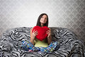 Portrait of a girl with a red heart cushion sweet sitting on the sofa and looking up Royalty Free Stock Photos