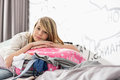 Portrait of girl relaxing on bulging suitcase at home Royalty Free Stock Photo