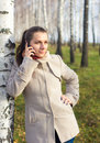 Portrait of a girl under the birch with phone Royalty Free Stock Image