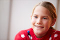 Portrait of girl wearing christmas jumper looking away from camera smiling Royalty Free Stock Photo