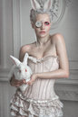 Portrait of a girl in a whight costume holding a white bunny Royalty Free Stock Photo